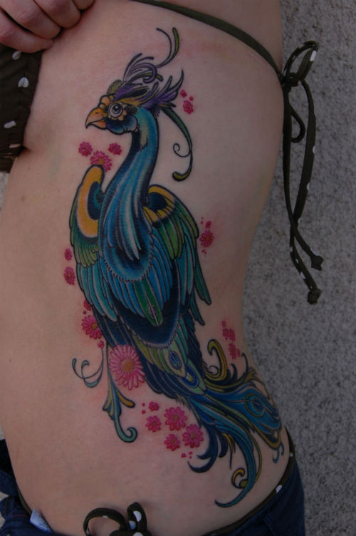 Bright and colorful bird tattoo on ribs