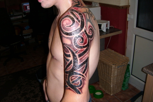 Red and black tribal arm tattoo for men
