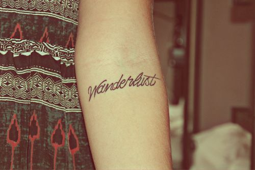 """Wanderlust"" Word Arm Tattoo"